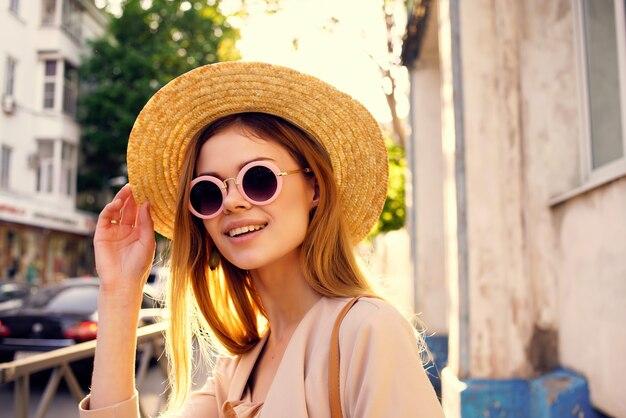Jolie femme dans la rue portant un chapeau et des lunettes lifestyle