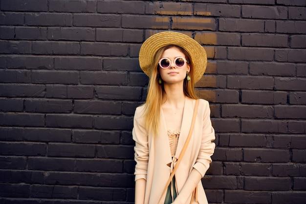 Jolie femme dans la rue portant un chapeau et des lunettes modèle de mur de briques noires