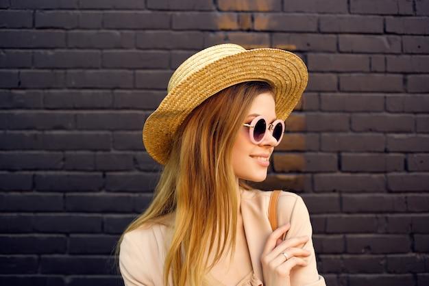 Jolie femme dans la rue portant chapeau et lunettes mur de briques noires