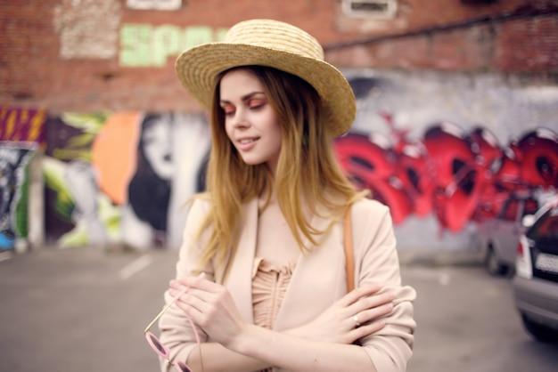 Jolie femme dans la rue portant un modèle de chapeau et de lunettes