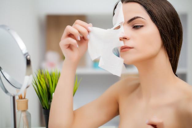 Jolie femme dans la salle de bain faisant une procédure cosmétique pour les soins de la peau du visage