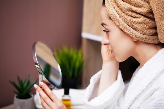 Jolie femme dans la salle de bain faisant une procédure esthétique pour les soins de la peau du visage