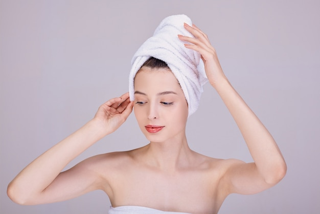 Jolie femme dans une serviette tient sa tête dans ses mains