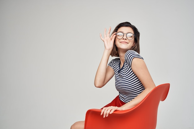 Jolie femme dans des vêtements à la mode assis sur la chaise rouge posing studio
