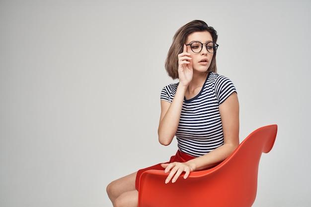 Jolie femme dans des vêtements à la mode assis sur la chaise rouge
