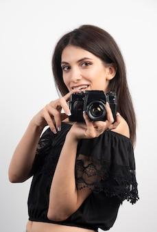 Jolie femme debout avec un appareil photo