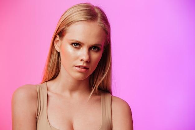 Jolie femme debout et posant sur le mur rose