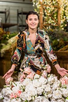 Jolie femme debout près de fleurs roses
