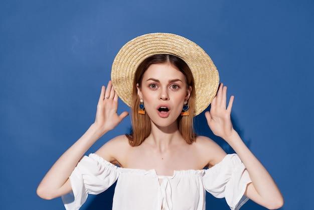 Jolie femme en décoration de chapeau posant fond bleu studio