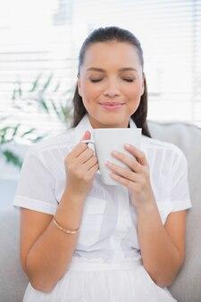Jolie femme détendue, sentant le café chaud
