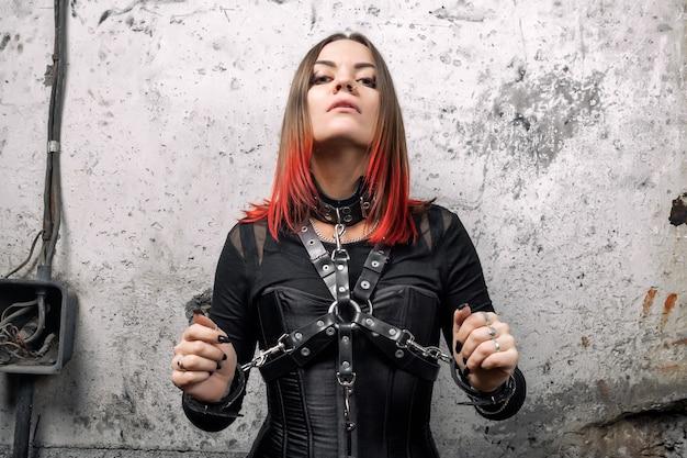 Jolie femme dominante avec des piercings et des cheveux brillants dans un corset noir, avec des harnais en cuir et des bracelets posant