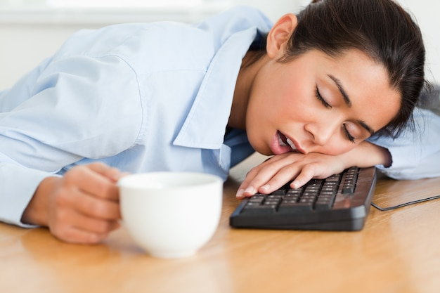 Jolie femme dormant sur un clavier tout en tenant une tasse de café