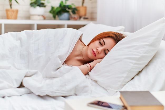 Jolie femme dort avec les deux mains sous sa tête sur un oreiller dans un lit léger