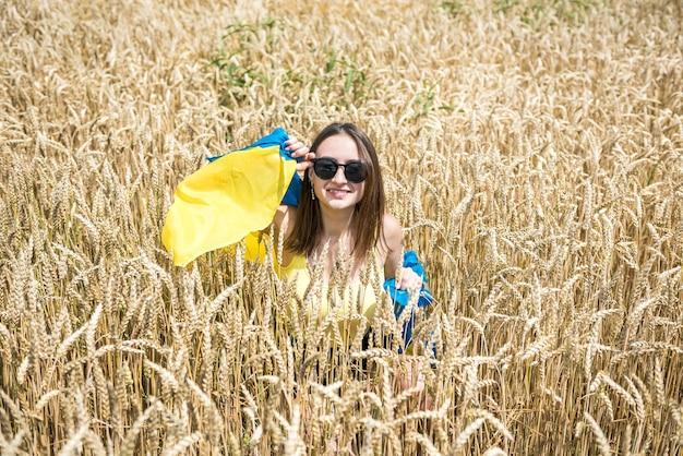 Jolie femme avec le drapeau de l'ukraine en champ de blé