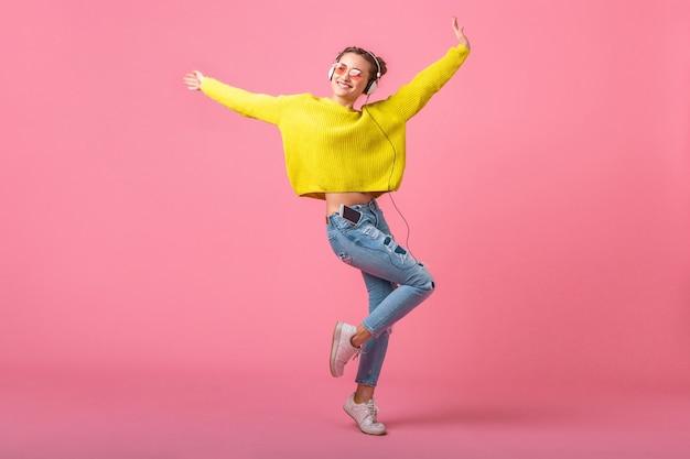 Jolie femme drôle heureuse sautant écouter de la musique dans des écouteurs habillés en tenue de style coloré hipster isolé sur un mur rose, portant un pull jaune et des lunettes de soleil, s'amuser