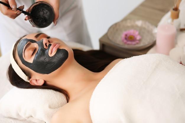 Jolie femme drôle avec un masque d'argile sur son visage