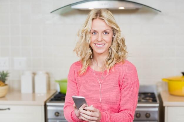 Jolie femme écoutant de la musique avec des écouteurs dans la cuisine