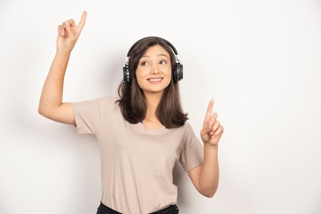 Jolie femme écoutant de la musique avec ses écouteurs sur fond blanc.