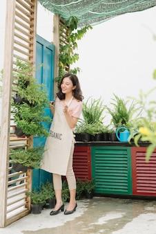 Jolie femme élagage des arbres avec sécateur dans le jardin