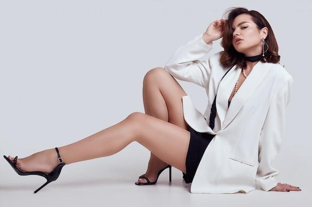 Jolie femme élégante aux cheveux noirs en costume de mode blanc