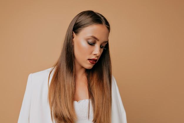 Jolie femme élégante aux longs cheveux bruns et rouge à lèvres vin qui pose en studio
