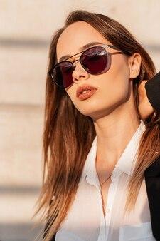 Jolie femme élégante dans des lunettes de soleil dans des vêtements à la mode dans la rue près d'un mur gris au coucher du soleil