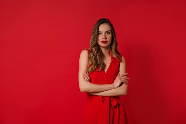 Jolie femme élégante et élégante aux cheveux ondulés, vêtue d'une robe rouge avec du rouge à lèvres rouge