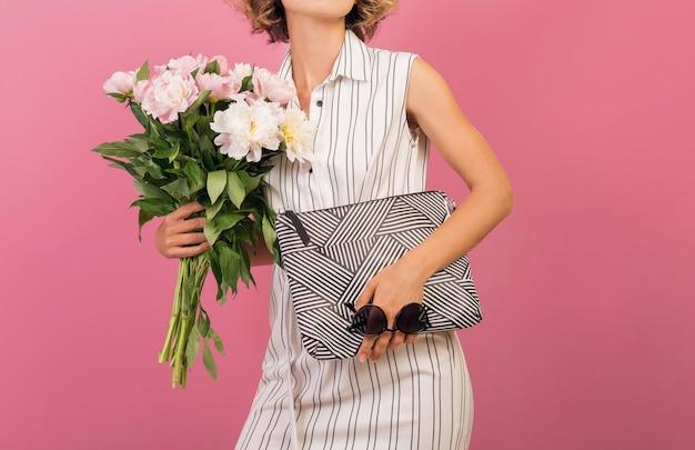 Jolie femme élégante en élégante robe rayée blanche sur fond rose studio expression du visage émotionnel, surpris, sac à main, bouquet de fleurs, coiffure drôle et frisée, accessoire de tendance mode été