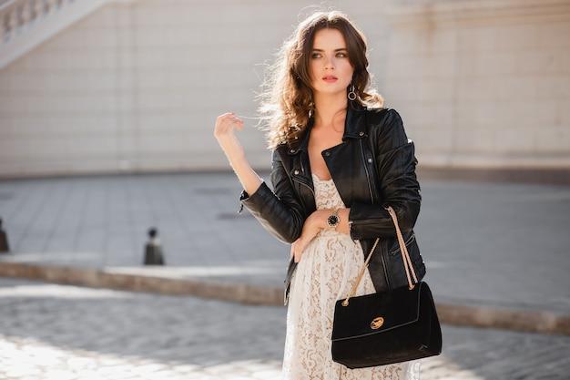 Jolie femme élégante marchant dans la rue en tenue à la mode, tenant un sac à main en daim, portant une veste en cuir noir et une robe en dentelle blanche, style printemps automne, agitant les cheveux au soleil, fashionista