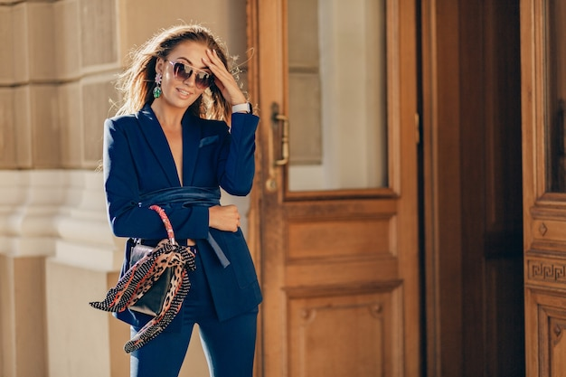 Jolie femme élégante portant un costume élégant bleu et des lunettes de soleil marchant dans la rue tenant le sac à main