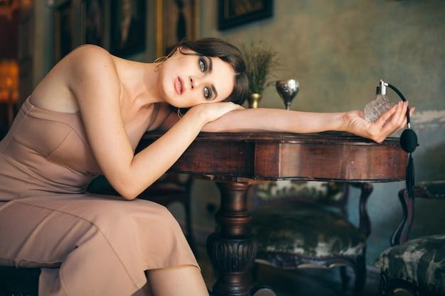 Jolie femme élégante sensuelle séduisante en robe boho assis vintage retro cafe holding parfum