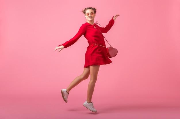 Jolie femme élégante souriante heureuse en robe à la mode rouge sautant en cours d'exécution sur un mur rose isolé, tendance de la mode printemps été, humeur romantique fille flirty