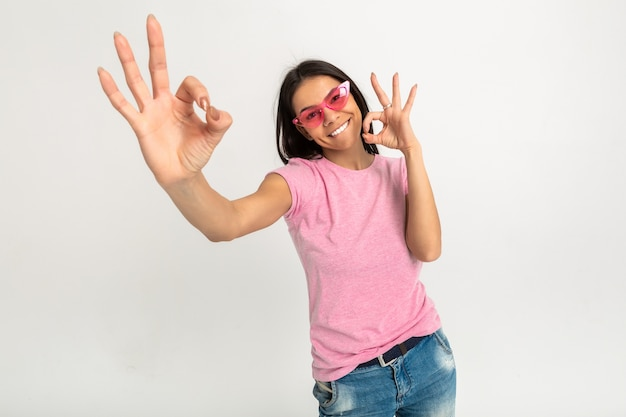 Jolie femme émotionnelle drôle heureuse en t-shirt rose bras isolés vers l'avant montrant signe ok