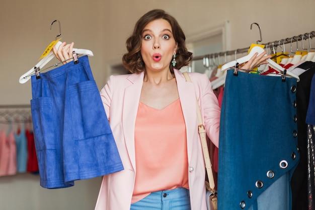 Jolie femme émotionnelle tenant des vêtements sur cintre dans un magasin de vêtements