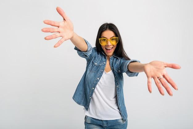 Jolie femme émotive riante bras ouverts à la caméra isolée sur studio blanc