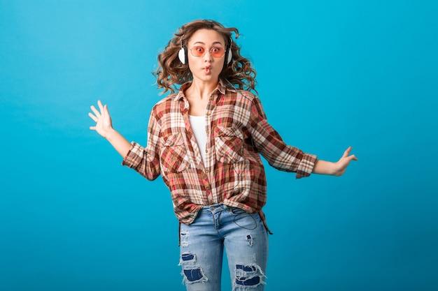 Jolie femme émotive souriante sautant avec l'expression du visage fou drôle en chemise à carreaux et jeans isolés sur fond bleu studio, portant des lunettes de soleil roses
