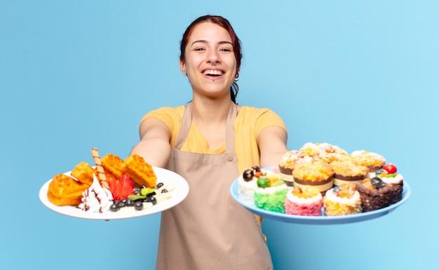 Jolie femme employée de boulangerie avec des gaufres et des gâteaux