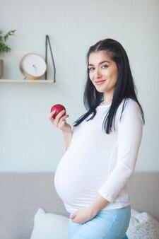 Jolie femme enceinte avec apple. attend femme tenant des aliments sains. dame mangeant une pomme rouge. une bonne nutrition pour la grossesse.