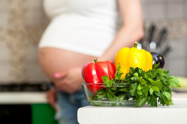 Jolie femme enceinte et une assiette avec des légumes et des herbes