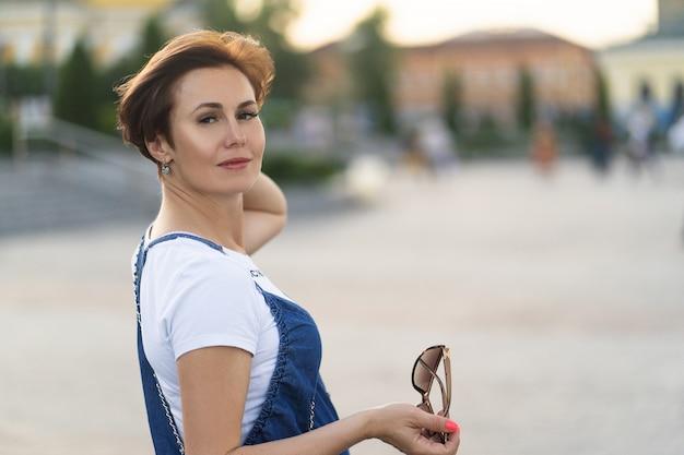 Jolie femme enceinte portant une tenue décontractée à la place de la ville