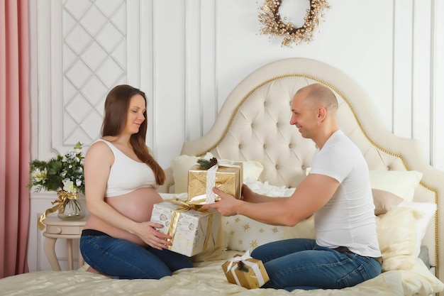 Jolie femme enceinte et son joli mari échangent des cadeaux de noël tout en passant du temps ensemble sur le lit