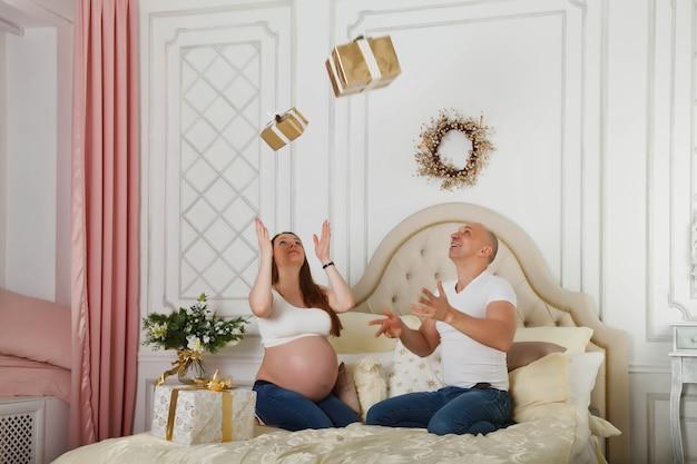 Jolie femme enceinte et son joli mari jettent un cadeau de noël