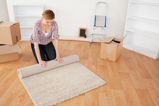 Jolie femme enroulant un tapis pour se préparer à déménager
