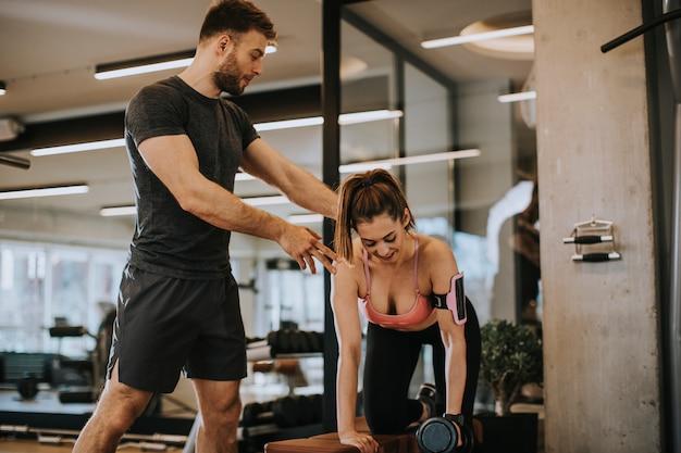 Jolie femme et un entraîneur personnel avec musculation au gymnase