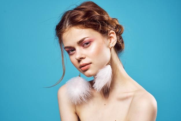 Jolie femme épaules nues boucles d'oreilles bijoux mode fond bleu