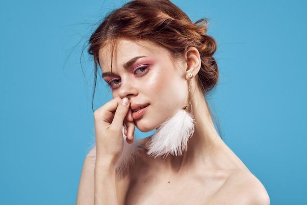 Jolie femme épaules nues boucles d'oreilles maquillage fraîcheur fond bleu.