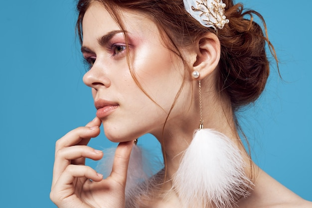 Jolie femme épaules nues boucles d'oreilles moelleuses maquillage lumineux close-up.
