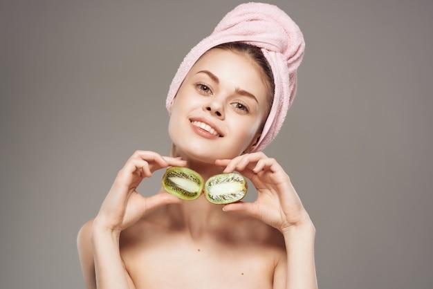 Jolie femme épaules nues avec des fruits kiwi en vue recadrée à la main