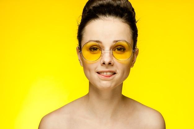 Jolie femme épaules nues lunettes jaunes glamour de la mode. photo de haute qualité