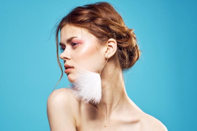 Jolie femme épaules nues maquillage lumineux boucles d'oreilles bijoux fond bleu